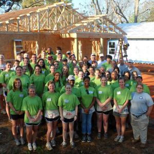 Large group of students stand in front of house they worked on with Habitat for Humanity